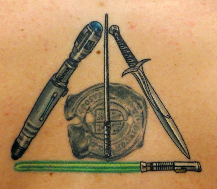 Nerd tattoo: Deathly Hallows symbol composed of Snape's wand, Luke's lightsaber, Sting from Lord of the Rings, the 10th Doctor Who's screwdriver, and the Goonies dubloon.  Done by Terry Grow at AAA tattoo, Lafayette, LA