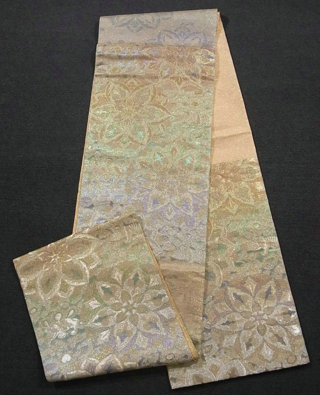 This is a brilliant Sahari Tsuzure Fukuro Obi. It enhances true jewel-like sparkles from allover by reflection, and it will take your breath away... It has 'doukyo'(copper mirror) pattern, which is woven with shining seven color threads.
