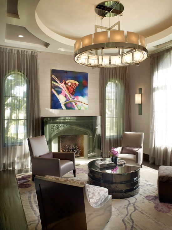 Living Room Funky Chair Design, Pictures, Remodel, Decor and Ideas - Note the radial balance from the circular chair arrangment around the round coffee table with a circular chandelier in neutral colors.  The painting with bright clors supports the focal point, the green fireplace.  Note the hint of violet in the rug, flowers and painting.