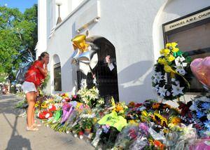 銃乱射事件が起きたエマニュエル・アフリカン・メソジスト・エピスコパル教会には朝から市民が訪れた。大学生の女性は花束を手向けた直後に泣き崩れた=19日午前、米サウスカロライナ州チャールストン、金成隆一撮影