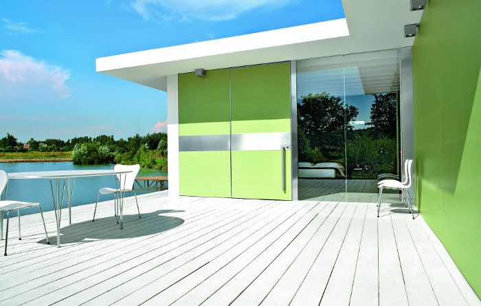 Synua pivot door with Synua Wall System in apple porcelain gres with stainless steel sector by Oikos Venezia.  www.oikos.it