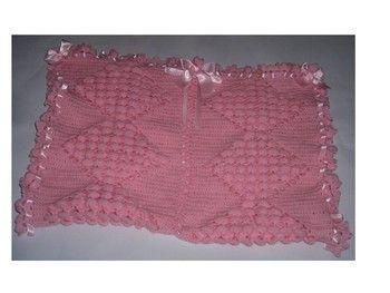 Superbe Couverture pour Bébé, fait mains au crochet Indispensable pour garder Bébé bien au chaud, pour les petits câlins, pour lui donner le biberon, ou juste pour l'envelopper. Cette jolie couverture vous servira pour le berceau, le landau, le couffin, etc... De couleur rose. Longueur : 85 cm Largeur : 56 cm Ornée de nœud et de ruban en satin rose. Laine utilisée : cheval blanc pour bébé : 100% acrylique. Idéal pour faire un Cadeau de Naissance, de Baptême. A offrir ou à s'offrir