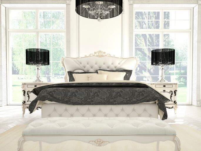 This monochromatic bedroom features elegant detailing on the furniture, bold patterning on the bed linens, and a striking chandelier over the large bed.
