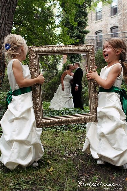 unique wedding photo shots with flower girls holding a picture frame over a bride and groom