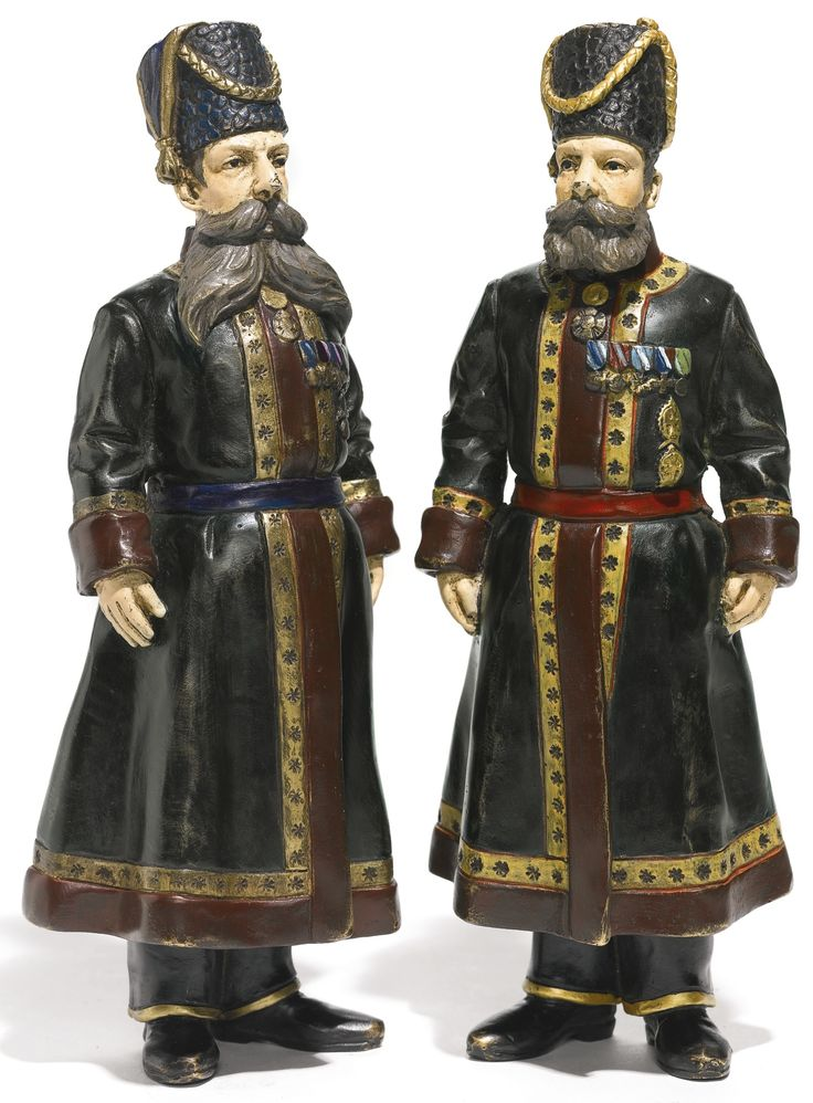 A pair of bronze figures, inscribed Fabergé, dated 1912 cast and cold painted as A.A. Kudinov and N.N. Pustynnikov, personal Kamer-Kazak bodyguards of Dowager Empress Maria Feodorovna and Empress Alexandra Feodorovna, in dress parade uniforms with badges and medals, the coats trimmed with Imperial eagles, the cockaded fleece hats with gold braid, inscribed in Russian on the heels and soles of the boots 'Kamer-Kazak since 1894