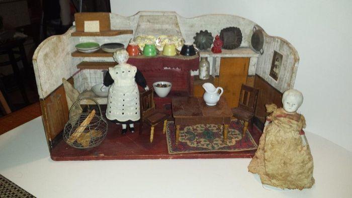 ca 1890 - China-head en Parian  Houten, in mooie staat verkerend geschilderd keukentje, afmetingen 43 x 23 x 15 cm. Toebehoren: vloerkleedje, tafel, twee stoeltjes, vier kop-en-schoteltjes, gemerkt 'Foreign', mandje haardhout, koffiemolentje en ornament met schaap, 4 bakblikjes, twee witte kommen, porseleinen kruikje en fles. Kastdeurtje kan open.  Het dienstmeisje met China-head is in authentieke, zeer goede staat, evenals de katoenen kleding. De dame met Parian-kopje is ook in authentieke…