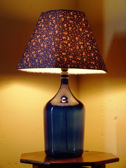 Luminária com base de garrafão de vinho e cúpula sextavada em tecido de algodão floral. R$ 139,90