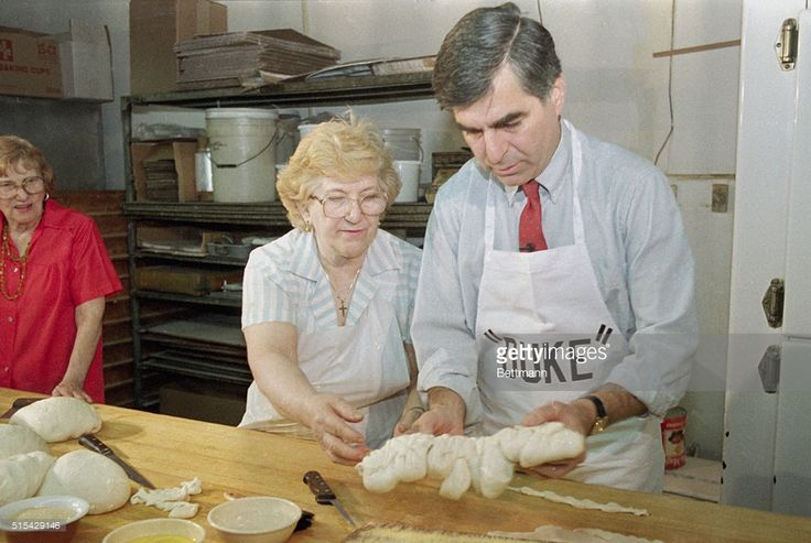 Massachusetts Gov. Michael Dukakis, tries his hand at making bread at a neighborhood bakery under the watchful eye of Annitte Shrategrano. Dukakis will be trying to win the Democratic primary in Illinois. Dukakis, the front runner for the Democratic nomination, is trailing Sen. Paul Simon and the Rev. Jesse Jackson in polls of Illinois voters.