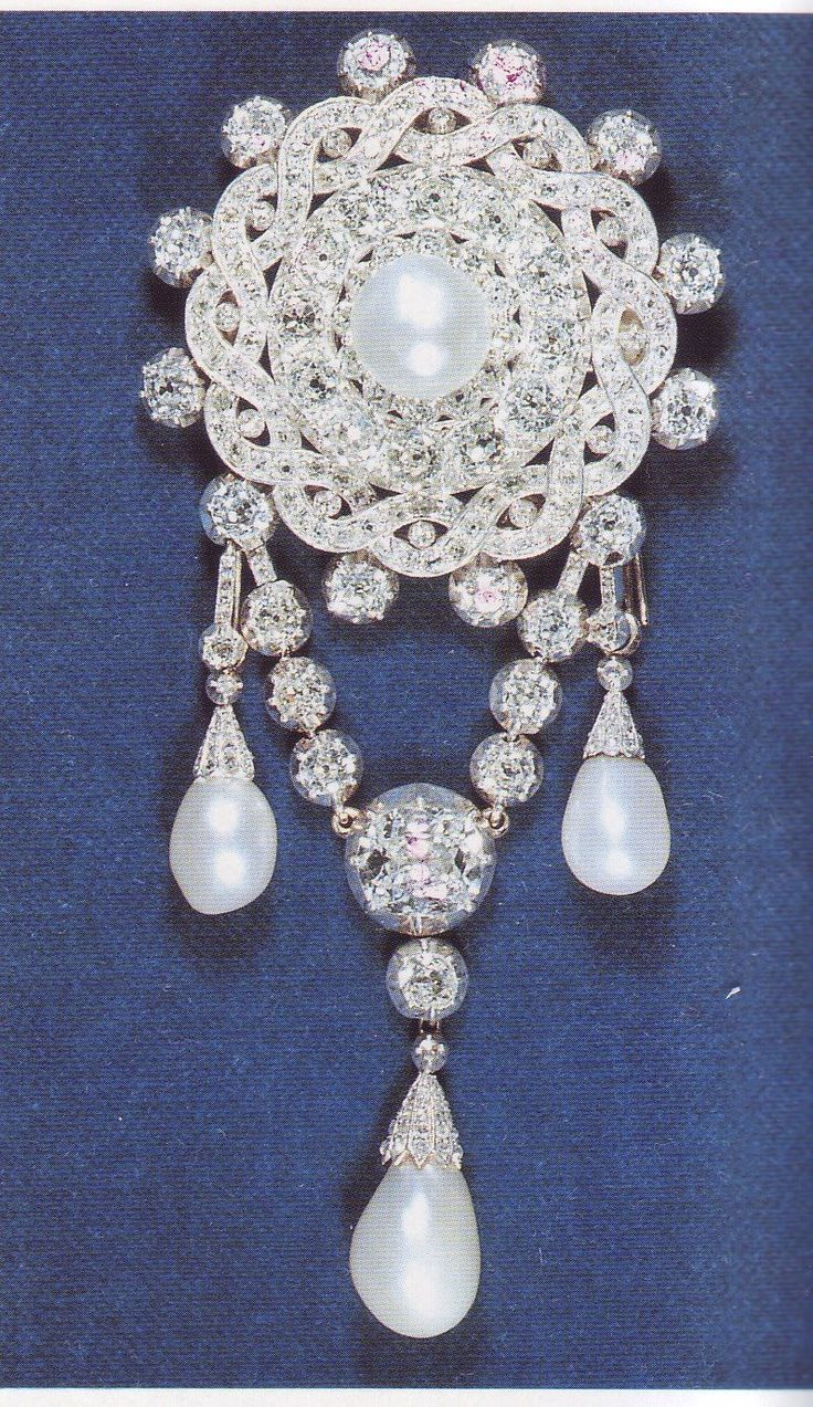The Dutchess of Teck's Corsage Brooch. This corsage jewel is typically Victorian in design. The brooch consists of a large pearl set in a circle of diamonds enclosed in a diamond plaited scroll frame with twelve collet stones set around the edge. A U-shaped chain of large collet diamonds ends in three pendant drops.