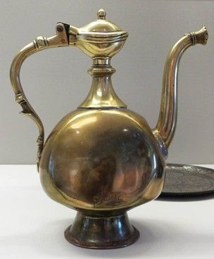 Ewer made of cast and beaten brass; with hinged lid, the juncture between body and spout repaired, and highly polished all over. Two inscriptions.