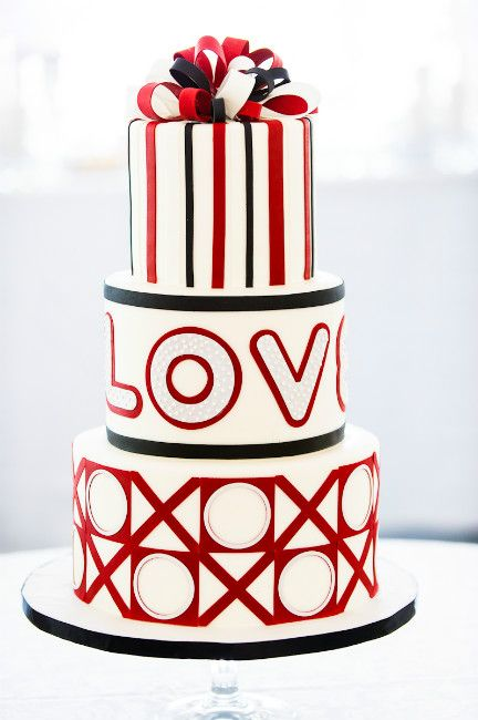 A modern three-tiered red, black and white wedding cake with fondant LOVE, X's and O's & ribbon bows on top