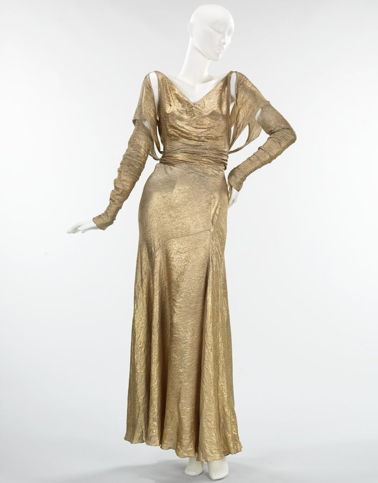 Evening Dress Jessie Franklin Turner 1933 Lamé, a fabric which incorporates metallic threads and is known for its festive brightness, was often used in evening wear of the 1920s, '30s and '40s. The lamé used here is in relatively bright condition, allowing one to imagine its original effect of shining like liquid metal. Jessie Franklin Turner, the designer of this dress, was widely known for her evening wear. This example demonstrates one reason for her renown, as it incorporates pristine…