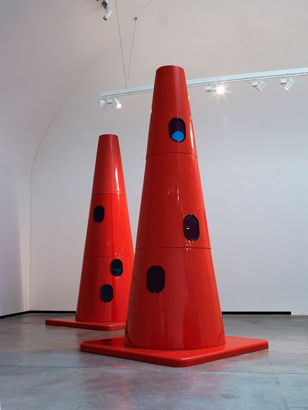 Dennis Oppenheim - Safety Cones - 2007 18' H x 9' W x 9' D Blaze orange cast fiberglass, steel and acrylic windows  By increasing the dimensions of the familiar, simple geometric form the structure begins a dialogue with architecture rather than object. Because of the considerable presence of the fluorescent conic markers they are contemporary totems, which immediately repel proximity. As an architectural structure they say 'stay away, beware, danger'.