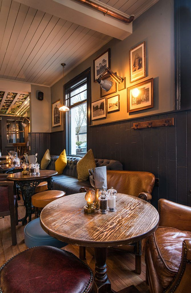 Interior decor inspiration, mustard velvet chairs, blue tiled fireplace, upcycled wine bottle ceiling ideas in traditional English pub restaurant In the midst of a vibrant area of Cambridge, The Petersfield is a traditional British pub, the perfect place for afterwork drinks with colleagues and friends. www.thepetersfield.co.uk