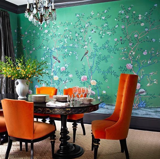 This homeowner fell in love with this whimsical, hand-painted silk wall covering from de Gournay. Its cheerful songbirds, along with the bold tangerine velvet of the vintage dining chairs, give the room a lighthearted air.