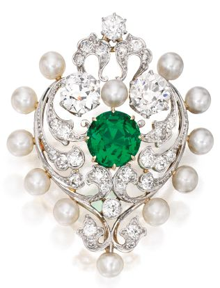 A Belle Époque Gold, Platinum, Emerald, Pearl and Diamond Brooch, Marcus & Co. Designed as a heart composed of scrollwork motifs, centring a round emerald, accented by two old European-cut diamonds, further set with smaller old European and old mine-cut diamonds, framed by 12 pearls, signed Marcus & Co., fitted with retractable pendant loop; circa 1900.