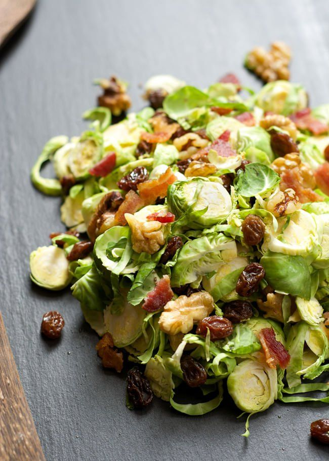 Delicately shaved brussels sprout salad tossed in a simple maple dijon vinaigrette, complete with crisp bacon and sweet raisins!
