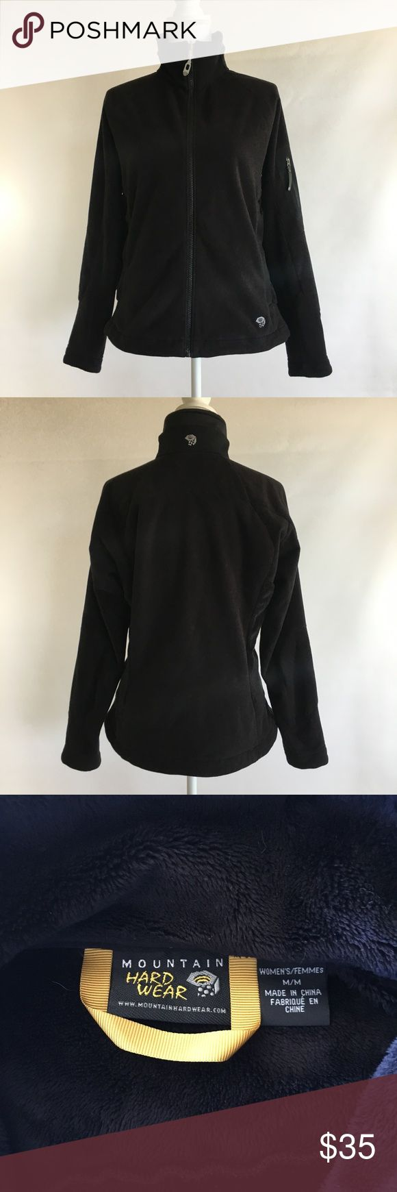 """Mountain Hardwear Women's m black fleece jacket Mountain Hardwear womens medium black fleece jacket The outside is mostly a thin pile fleece, the inside is thicker pile.  The sides have a thicker pile as well. The jacket is in great condition- no stains tears or holes and the fleece looks very nice, not overworn.  Zips down the front, zippered hand pockets at sides, one zippered arm pocket. Adjustable waist. Measurements: 22"""" across flat front of chest 26"""" in length from top of shoulder to…"""