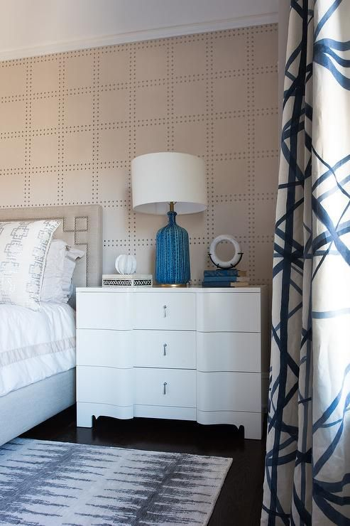 A  Bungalow 5 Bardot Dresser topped with an Aerin Culloden Table Lamp sits against an accent wall covered in Phillip Jeffries Rivet Wallpaper beside a light gray Greek key headboard with a nailhead trim positioned behind a bed dressed in light gray border hotel bedding topped with silver geometric pillows.