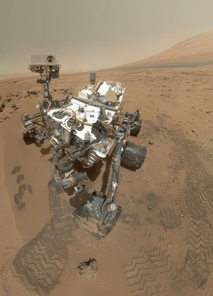 "On Sol 84 (Oct. 31, 2012), NASA's Curiosity rover used the Mars Hand Lens Imager (MAHLI) to capture this set of 55 high-resolution images, which were stitched together to create this full-color self-portrait.    The mosaic shows the rover at ""Rocknest,"" the spot in Gale Crater where the mission's first scoop sampling took place. Four scoop scars can be seen in the regolith in front of the rover."