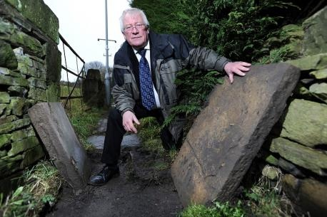 Councillor Mike Ellis with the damage to the lifted Yorkshire flags along a length of footpath in Wilsden
