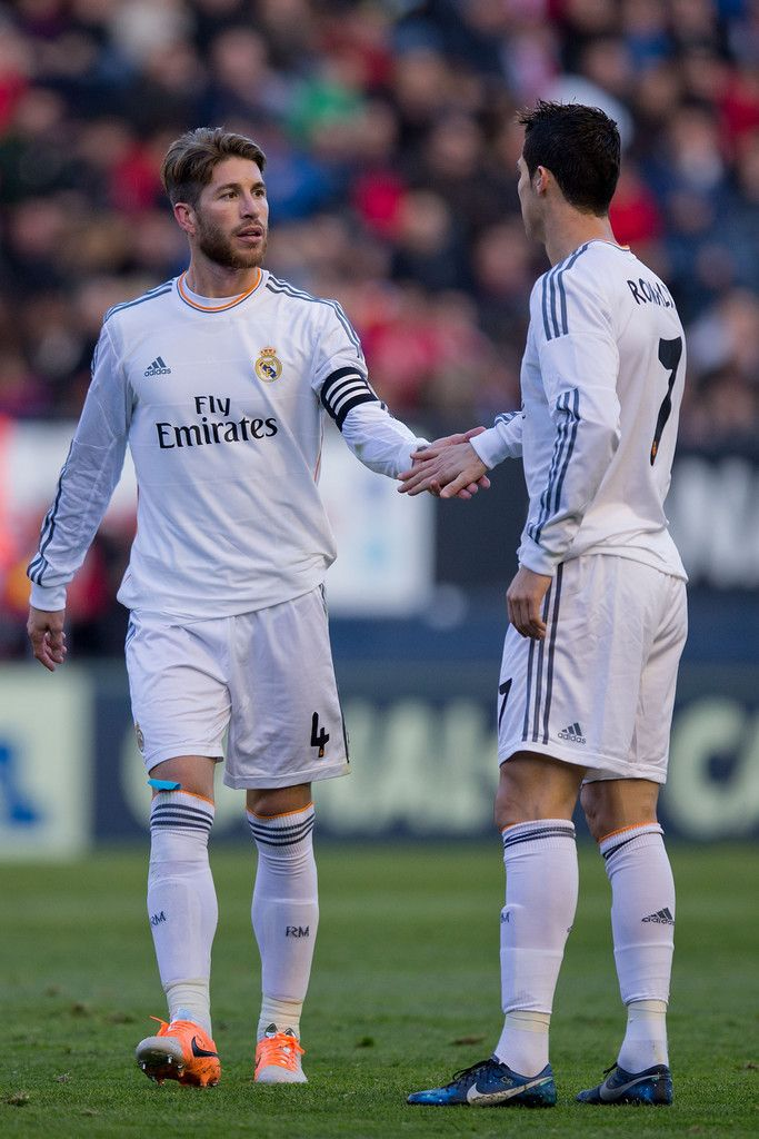 Sergio Ramos clashes hand with his teammate Cristiano Ronaldo during the La Liga match between CA Osasuna and Real Madrid CF at Estadio El Sadar de Navarra on December 14, 2013 in Pamplona, Spain.