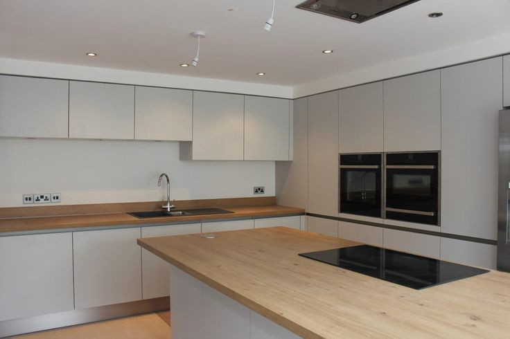 Large modern kitchen in a lovely pale grey in a matte finish with wooden worktops.