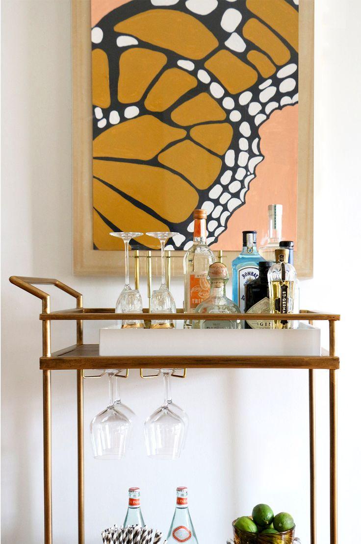 Brass bar cart underneath butterfly wing ar