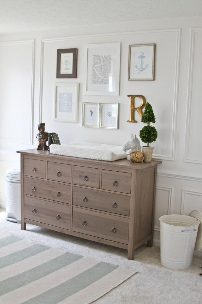 This gallery wall add interest to a white nursery with a gold monogram letter and different color frames.