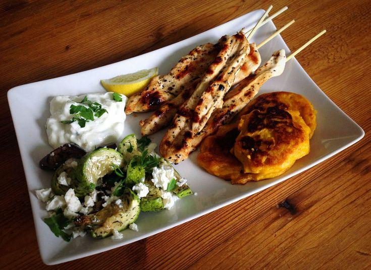 Griekse kip souvlaki met tzatziki, salade van gegrilde groenten en zoete aardappelkoekjes.
