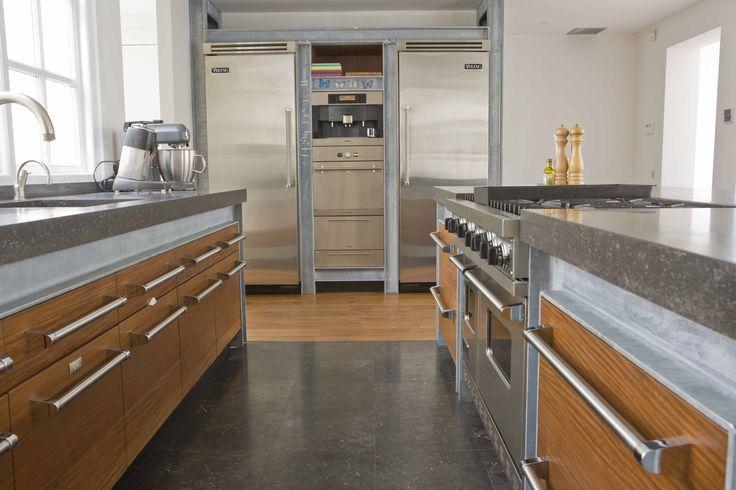 Maatwerk notenhouten keuken met Viking handgrepen en Viking apparatuur. Blad van beton en bladlijst, zijwanden en kroonlijst H-balken.
