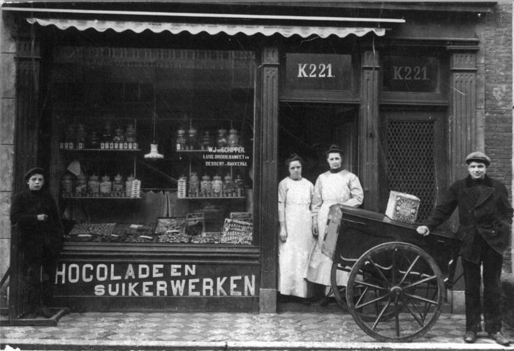 Kruidenierswinkel, om de voorgrond een verkoper met zijn handkar.