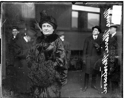 Unknown artist (Chicago Daily News). Mme. Maria Montessori, founder of the Montessori educational system, standing on the street in front of several unidentified men, 1913. Chicago Daily News negatives collection, Chicago Historical Society