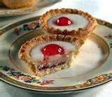'Cherry Bakewell Tart': shortcrust pastry shell,spread with jam and covered with a sponge-like filling with ground almonds(known as frangipane)covered with a top layer of almond flavoured icing and a single half glacé cherry.Lemon Bakewells with lemon flavoured fondant are also produced.Recipes abound with old and new recipes & modern examples are to be found in most cake shops and in most supermarkets.Alternative  flavors,include blackcurrant, strawberry & apple.Off shoot of  Bakewell…
