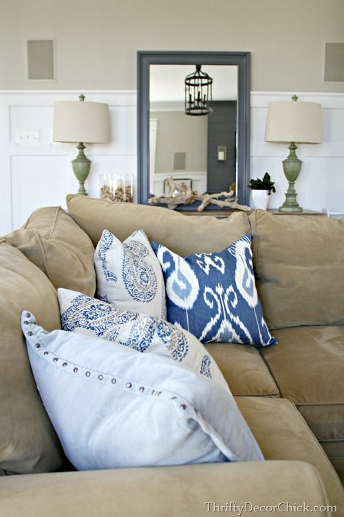 Plush tan couch with blue and white throw pillows