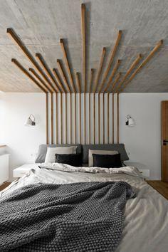 Tête de lit théâtralisée en tasseaux de bois.