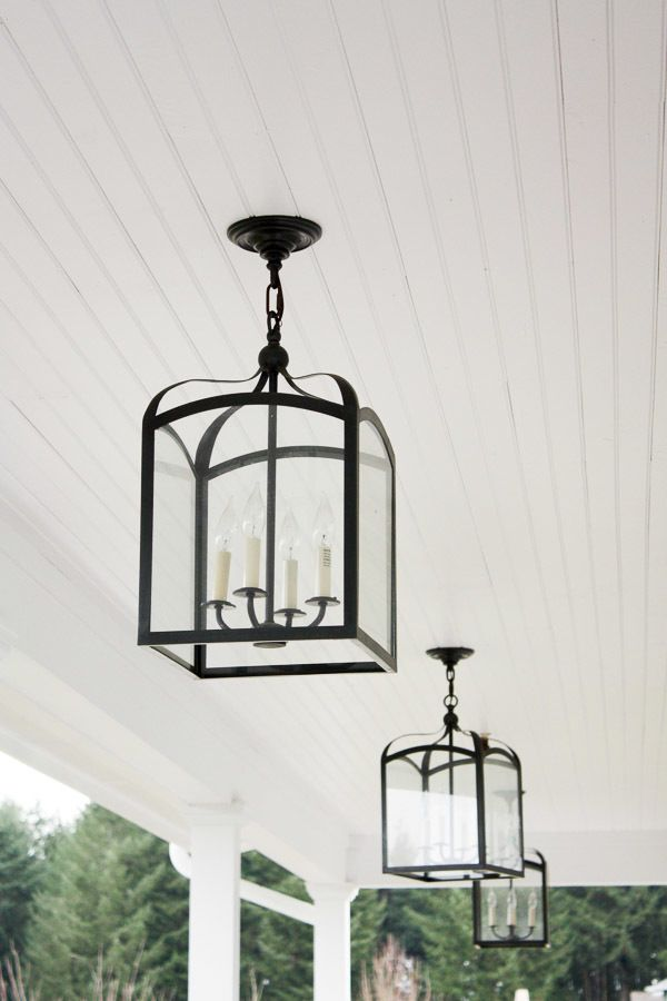 a line of black carriage lanterns on the beadboard ceiling of a back porch