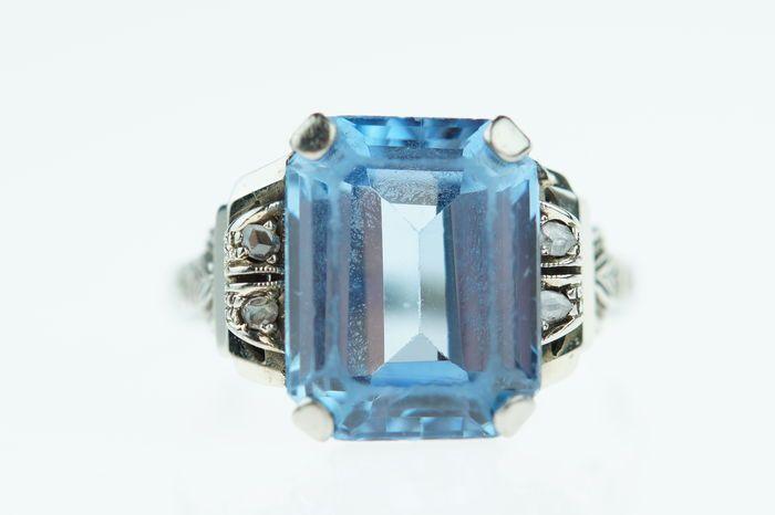 18 karaats gouden damesring bezet met blauwe topaas en roosgeslepen diamanten ringmaat 185  Witgouden damesring bezet met blauwe topaas en geflankeerd door 4 roosgeslepen diamantjes.Betreft een elegant en rijkelijk bewerkte ring met een gewicht van ruim 4 gram ringmaat 185 de kop van de ring is ca. 14x13mm.De ring verkeert in mooie staat(normale gebruikerssporen die je van een dergelijk sieraad mag verwachten facetranden topaas bovenop iets gesleten).Uiteraard is dit sieraad voorzien het 18…