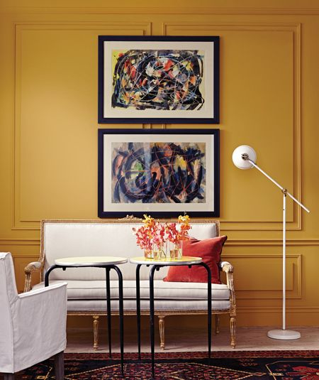 Soft golden wainscotting adorned with pair of black framed abstract art.