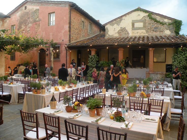 Guests start arriving to the rehearsal dinner in the Tuscan village. Pizza in the wood oven and pasta choices cooked in front of the guests Buffet style simple country with Tuscan red wine served in Fiasco - typical bottle. All Rights Reserved GUIDI LENCI www.guidilenci.com