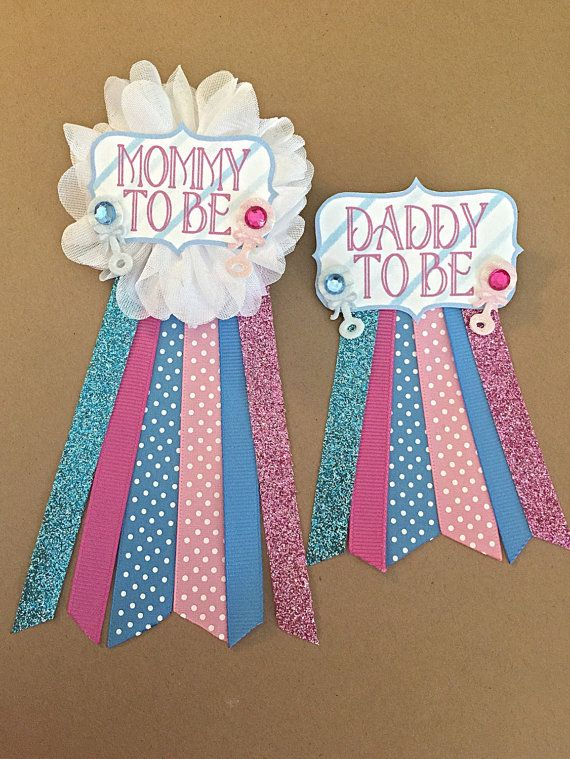 *****This includes both Mommy to be pin and smaller version Daddy to be pin. This pin is perfect for any gender neutral baby shower or gender reveal party! Can be pinned to any piece of clothing!  White flower corsage pin with blue and pink ribbons as pictured.  Tags Saying - Choose one: (Please include choices in order) Mommy Mommy to be Grandma Auntie *custom saying/name*  Tag Sticker - Choose one or two : (Please include choice in order) Pink rattle Pink baby bottle Pink baby footprint…