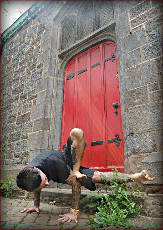 I love everything about this!  A guy with cool tattoos doing yoga in front of an awesome red door!!!