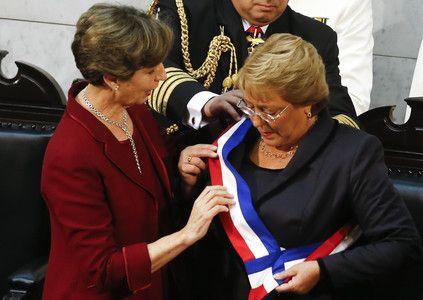 Isabel Allende, hija del presidente derrocado por la dictadura de Pinochet, coloca la banda presidencial a Michelle Bachelet, hija de un militar leal a Allende.