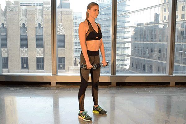 Stand with feet hip-width apart, holding the dumbbells in front of thighs with palms facing body. With a slight bend in knees, push hips back and slowly slide weights down legs toward floor while keeping spine long and abs tight. Push through the heels to return to standing.