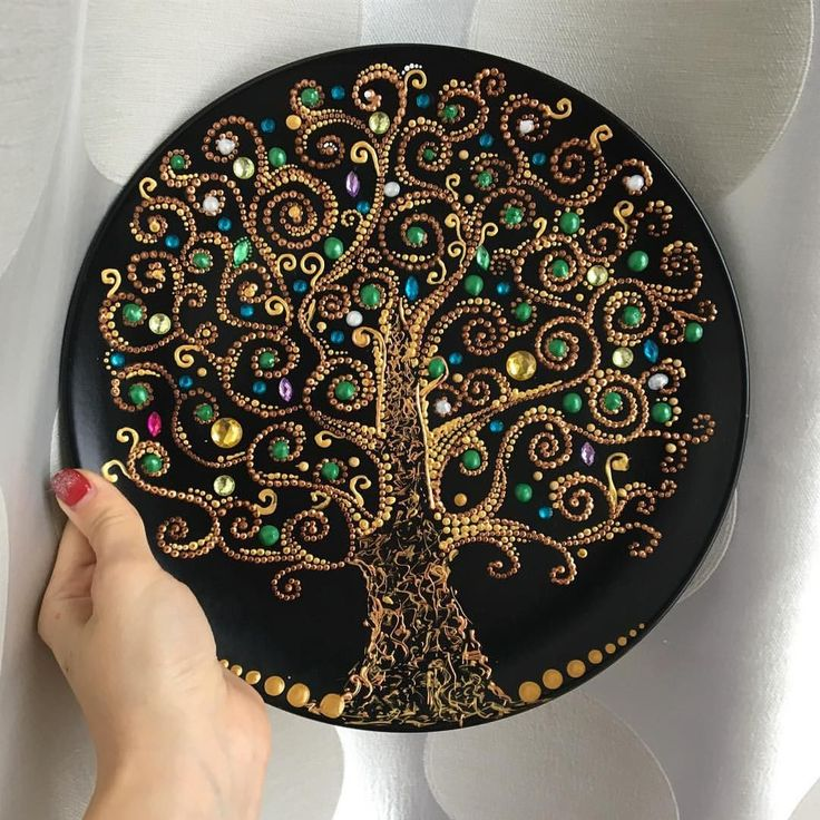 Tree using dot painting and sequins. Pretty big for a rock but may be usable on a plate or even a glass design