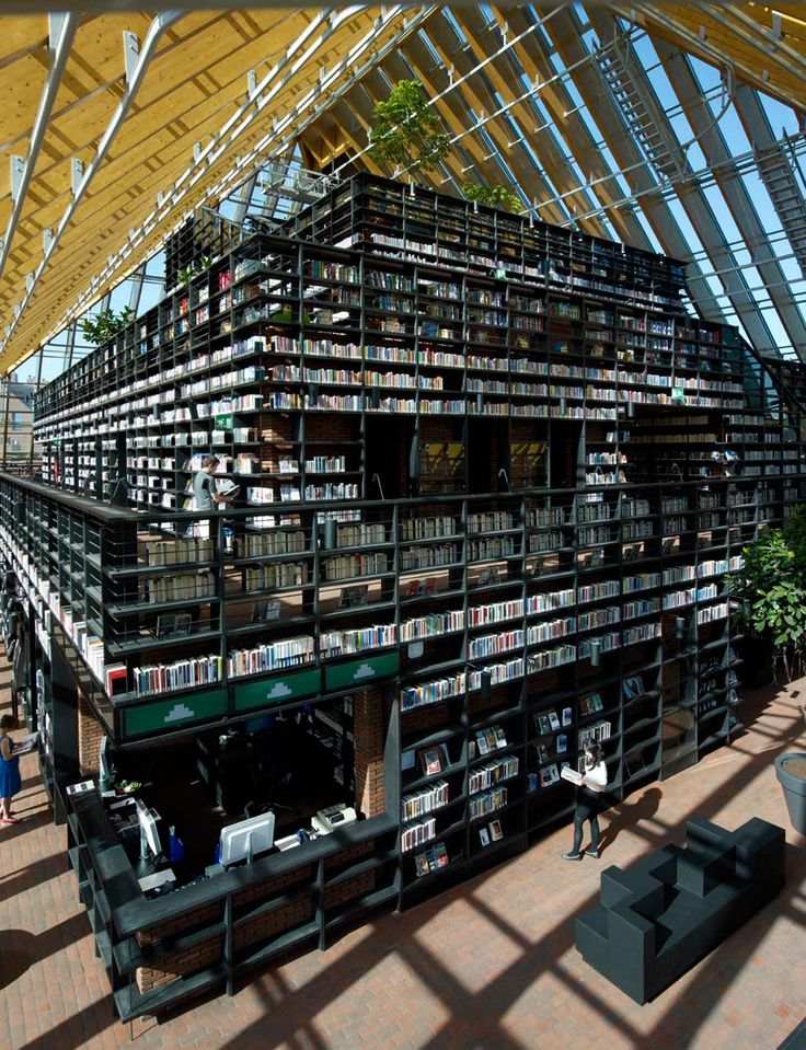a mountain of bookshelves is contained by a glass-enclosed structure and pyramidal roof with a total surface area of 9,300 square meters.