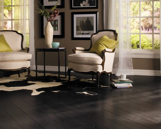 Dark laminate flooring in this black and white room with a few pops of color make a sophisticated look affordable.