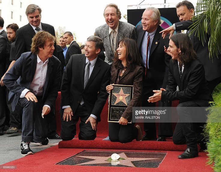 Paul McCartney smiles as he finished cleaning the star as (L-R) Hollywood Chamber of Commerce President and CEO Leron Gubler, Eric Idle, Olivia Harrison, city council member Tom LaBonge, Dhani Harrison and Tom Hanks laugh at a ceremony for Beatles legend George Harrison to posthumously received a star on the Hollywood Walk of Fame in Los Angeles on April 14, 2009. AFP PHOTO/Mark RALSTON