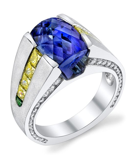 Platinum gents ring featuring a 7.03ct diamond back cut tanzanite accented with 1.44ctw of yellow diamonds, 1.24ctw of white diamonds, and 0.10ctw of demantoid garnets. This piece is available for rep