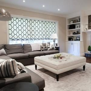 family room-- light tan walls w/white moldings, gray colored area rug, white ottoman